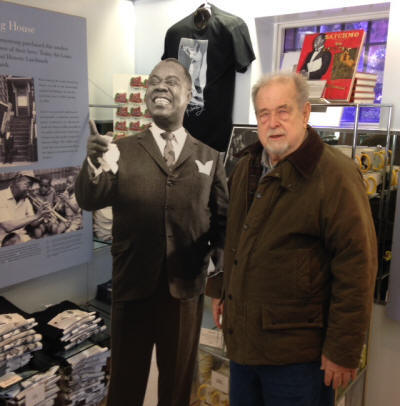 Bob Ringwald posing with a cardboard cut out of Louis Armstrong